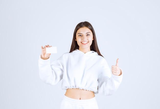 Ritratto di un modello di ragazza felice con una carta che mostra un pollice in su.
