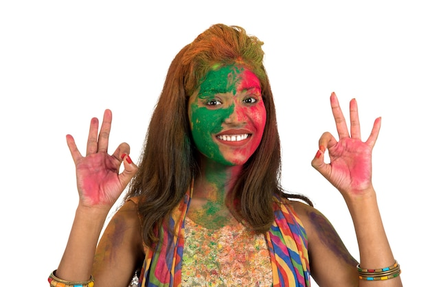 Portrait of a happy young girl with a colorful face on holi color festival on white background