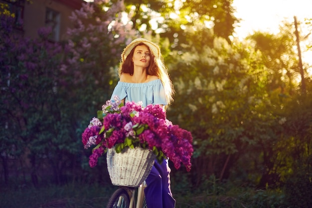 Portrait of a happy young girl with vintage bicycle and flowers on city background in the sunlight outdoor.