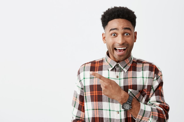 Portrait of happy young good-looking tan-skinned male student with afro hairstyle in casual checkered shirt smiling, pointing aside with finger with excited face expression