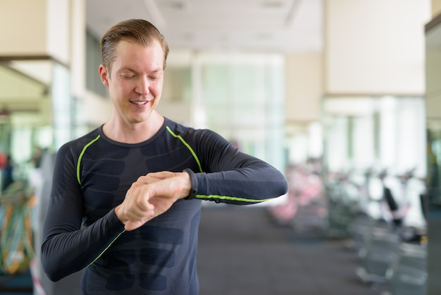 Portrait of happy young handsome man checking smartwatch at the gym during covid-19