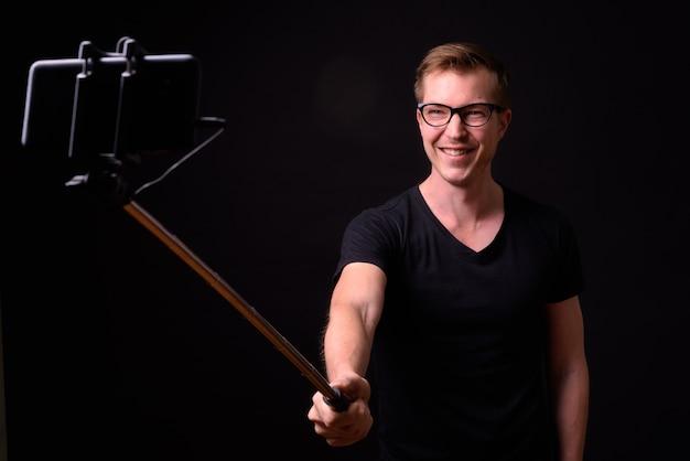 Portrait of happy young handsome nerd man taking selfie with phone on selfie stick