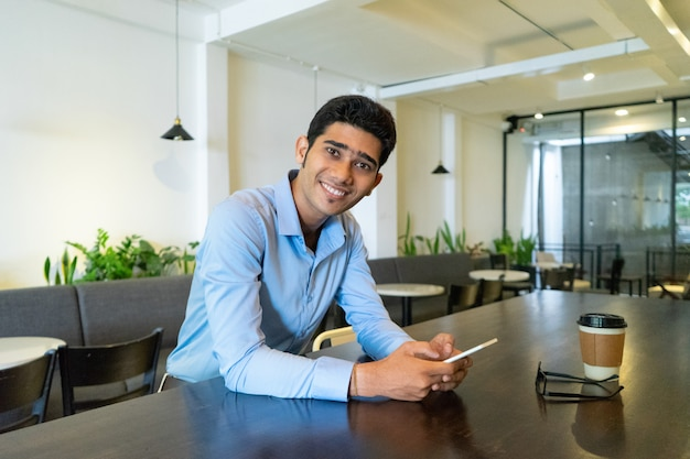 Portrait of happy young indian businessman sitting in cafe.