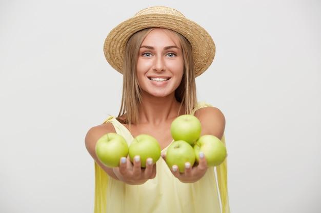 Ritratto di felice giovane donna bionda dai capelli lunghi con acconciatura casual tenendo le mani alzate con mele verdi e sorridente piacevolmente, isolato su sfondo bianco