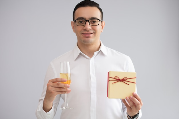 Portrait of happy young man holding champagne flute and gift box