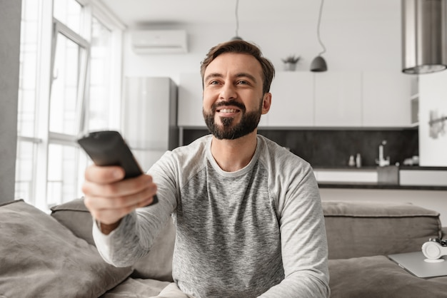 Portrait of a happy young man holding tv remote control
