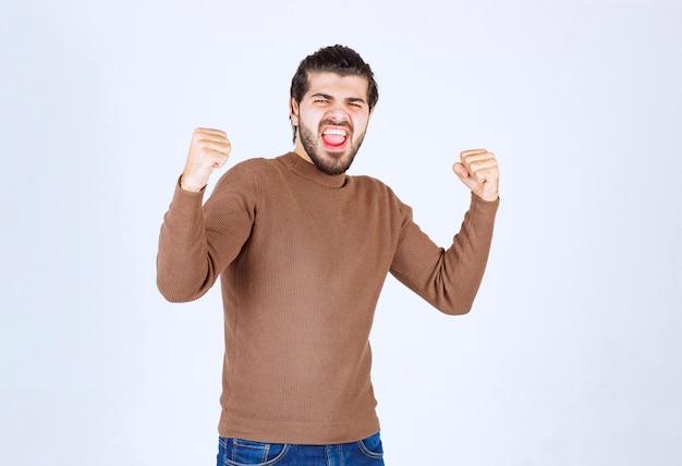 Ritratto di un modello felice del giovane nella riuscita posa.