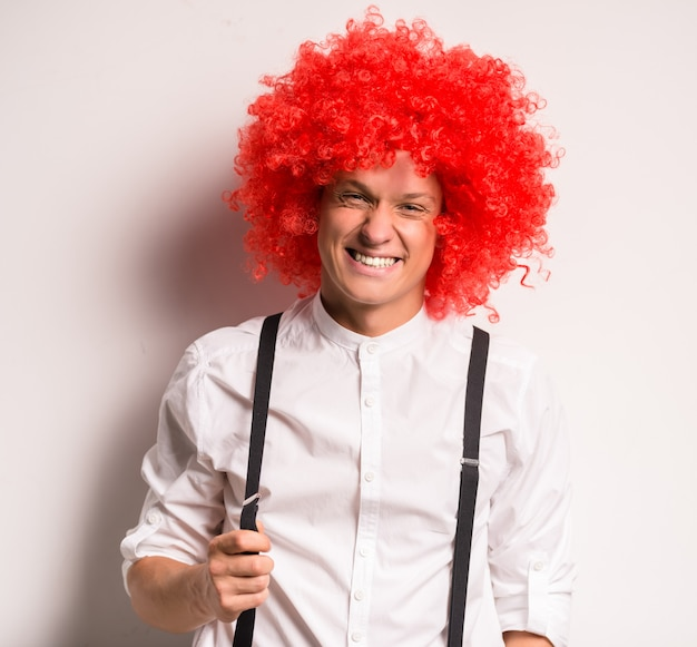 Portrait of a happy young man in a red wig.