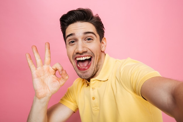 Portrait of a happy young man showing ok gesture