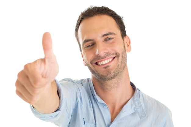 Portrait of a happy young man showing thumb up sign isolated on white background