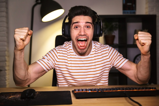 Portrait of happy young man yelling while playing video games on computer, wearing headphones and using backlit colorful keyboard