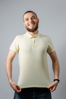 Portrait of a happy young man in yellow mocap t-shirt on gray.