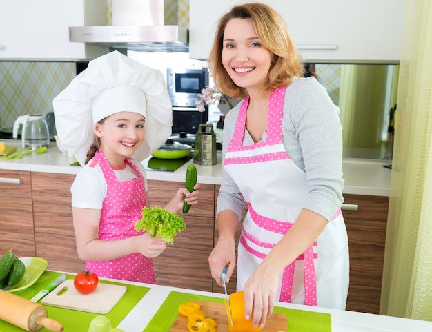 Portrait of happy young mother with daughter in pink apron cooking at the kitchen.