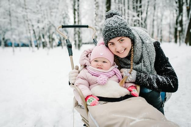 Портрет счастливой молодой матери с дочерью, стенд с младенцем в детских санках на открытом воздухе, на фоне зимы. закройте вверх. счастливая семья, прогулки в парке. младенец.