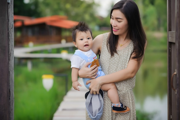 Portrait of happy young mother with little cute baby boy spending time together in summer park.