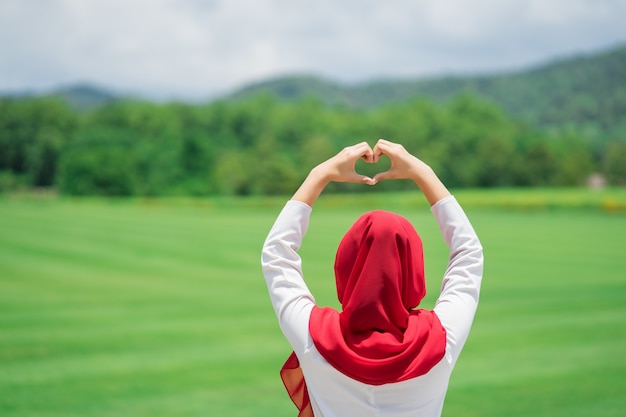 Portrait of happy young muslim red hijab at the green field