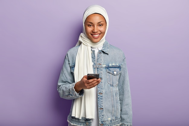 Portrait of happy young muslim woman posing with her phone