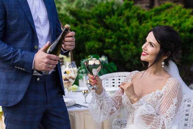 Portrait of a happy young newlywed couple celebrating wedding with champagne bottle at the park