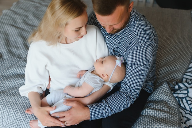 Portrait of happy young parents with baby in the bed at home