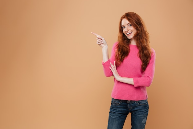 Portrait of a happy young redhead girl pointing finger at copyspace wall