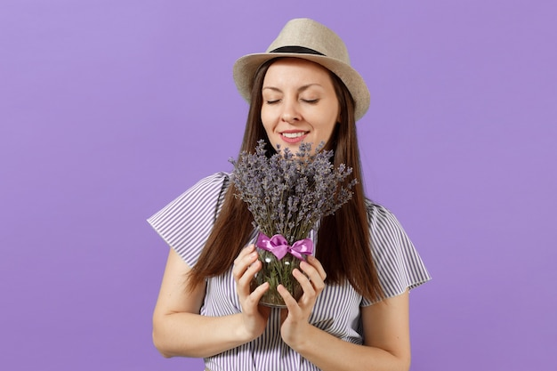 Portrait of happy young tender woman in blue dress straw hat hold and sniff bouquet of beautiful purple lavender flowers isolated on bright violet background. international women s day holiday concept