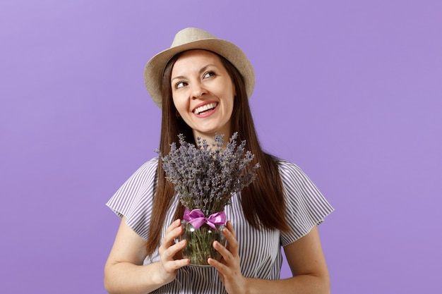 Portrait of happy young tender woman in blue dress straw hat holding bouquet of beautiful purple lavender flowers isolated on bright trending violet background. international women day holiday concept