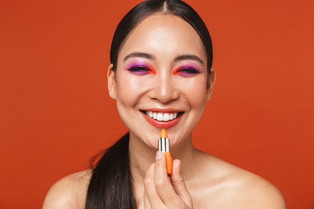 Portrait of a happy young topless asian woman with brunette hair wearing bright makeup, standing isolated on red, holding a lipstick
