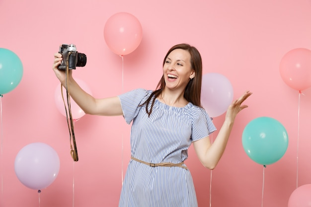 Portrait of happy young woman in blue dress doing selfie on retro vintage photo camera spreading hands on pink background with colorful air balloons. birthday holiday party people sincere emotions.