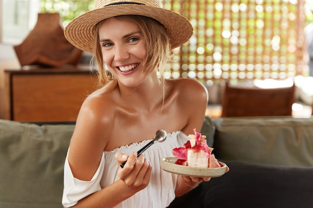 Portrait of happy young woman comes on summer party, celebrate something special, dressed in summer clothing, eats delicious cake, has glad positive expression. people, eating and rest concept