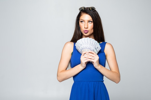 Il ritratto di una giovane donna felice si è vestito in vestito che giudica il mazzo di banconote dei soldi isolate