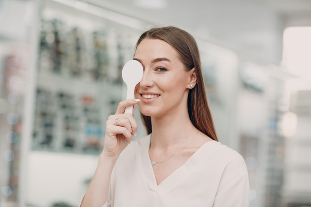 Portrait of happy young woman during eye exam at optometrist optician
