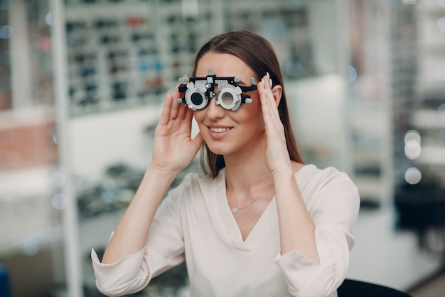 Portrait of happy young woman during eye exam with test goggles glasses at optometrist optician