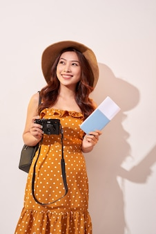 Portrait of a happy young woman in hat holding camera and showing passport while standing isolated over beige wall