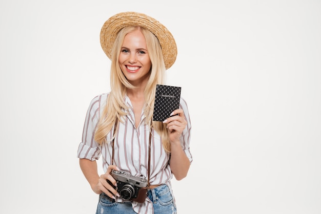 Portrait of a happy young woman in hat holding camera