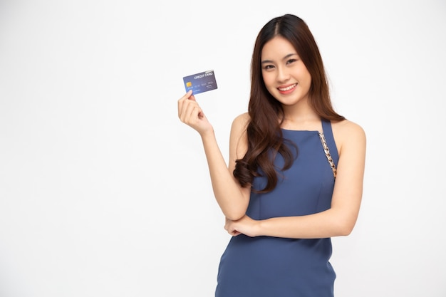 Portrait of a happy young woman holding atm or debit or credit card and using for online shopping spending a lot of money isolated, asian female model