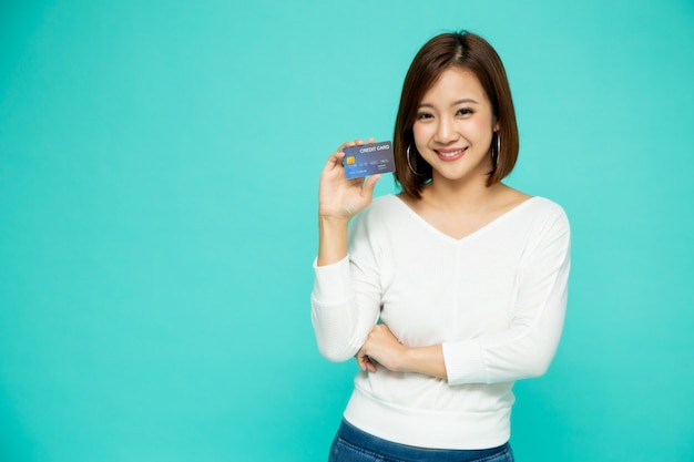 Portrait of a happy young woman holding atm or debit or credit card and using for online shopping spending a lot of money isolated over green wall, asian female model