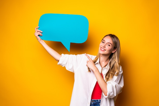 Portrait of a happy young woman holding empty speech bubble standing isolated over yellow wall