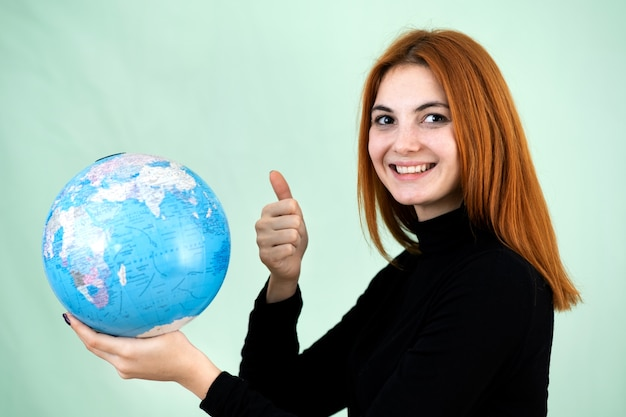 Portrait of a happy young woman holding geographic globe of the world in her hands.