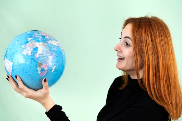 Portrait of a happy young woman holding geographic globe of the world