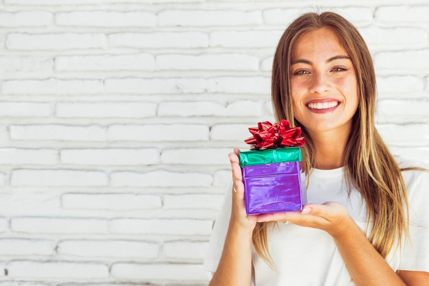 Portrait of a happy young woman holding gift box