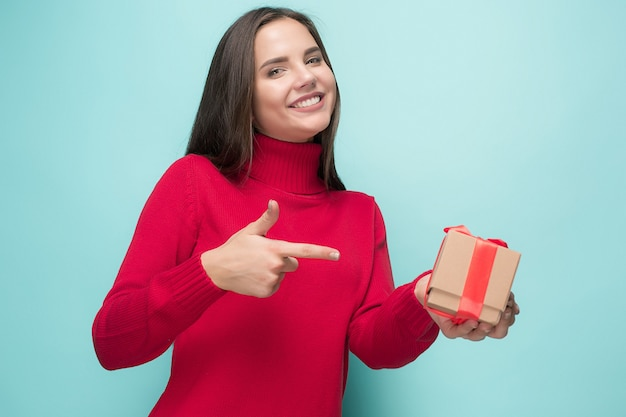 Portrait of happy young woman holding a gift isolated on blue