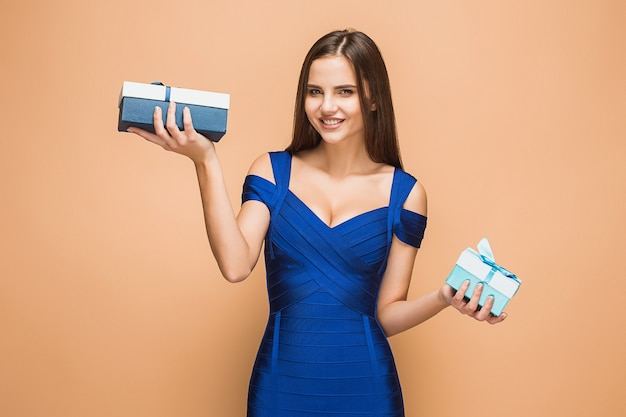 Portrait of happy young woman holding a gifts on brown