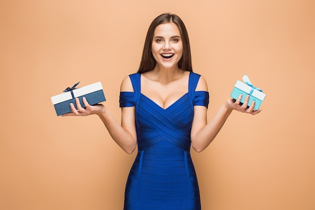Portrait of happy young woman holding a gifts isolated on brown studio background with happy emotions
