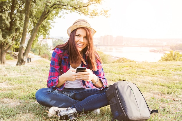 Portrait of a happy young woman holding mobile phone in park