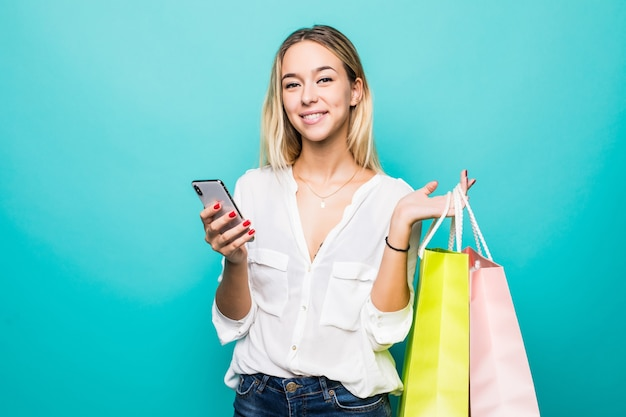 Portrait of a happy young woman holding shopping bags and mobile phone isolated on a mint wall