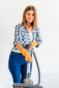 Portrait of a happy young woman holding vacuum cleaner