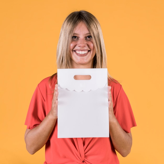 Portrait of happy young woman holding white paper bag