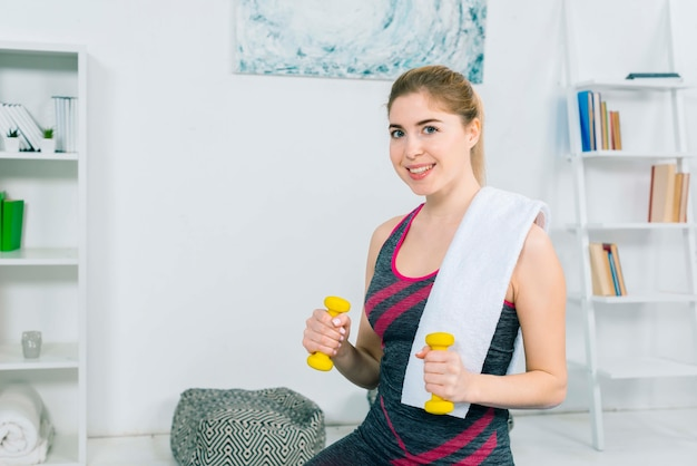 Portrait of happy young woman holding yellow dumbbells in hands with white napkin on shoulder