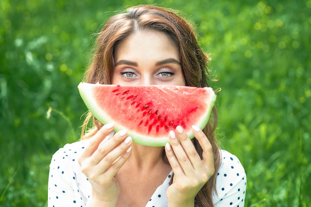 Portrait of happy young woman is holding slice of watermelon over green background.
