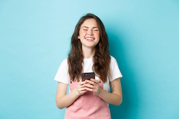 Ritratto di giovane donna felice che ride con lo smartphone in mano, sorridente e spensierata, utilizzando l'app mobile, in piedi su sfondo blu